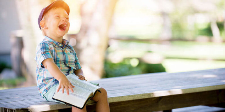 Kid Reading a Book and Laughing