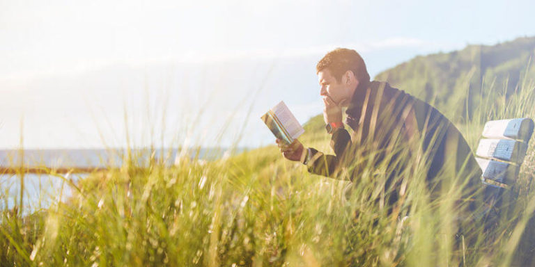 A Man Reading a Book Outdoor