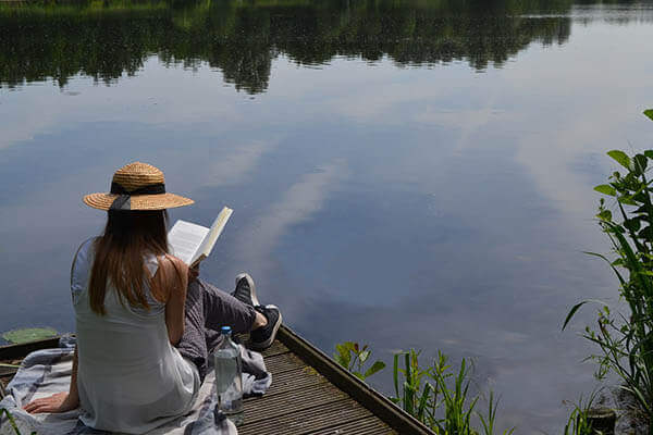 A girl reading a book on a platform near a lake