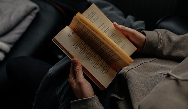 A man reading a mass-market paperback book
