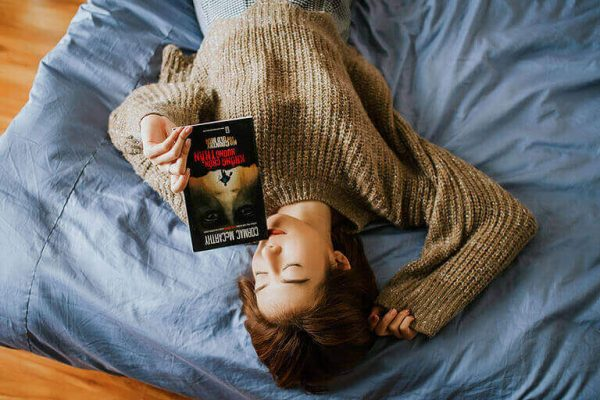 A girl lying on bed with a book in hand